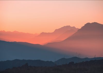 Mountain range in pink sunlight at sunset. Blue mountains with t